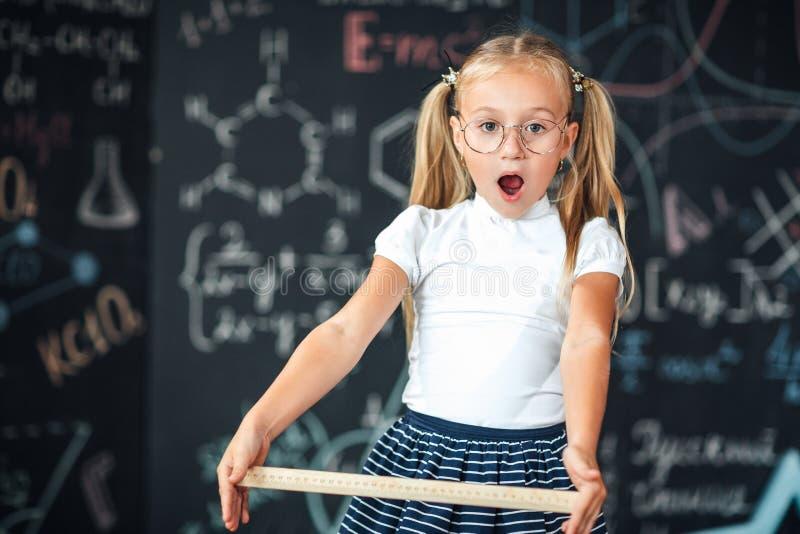 Piccolo ragazza bionda con un fronte sorpreso con un righello nella sua ragazza dell'allievo delle mani con i grandi righelli con immagini stock libere da diritti