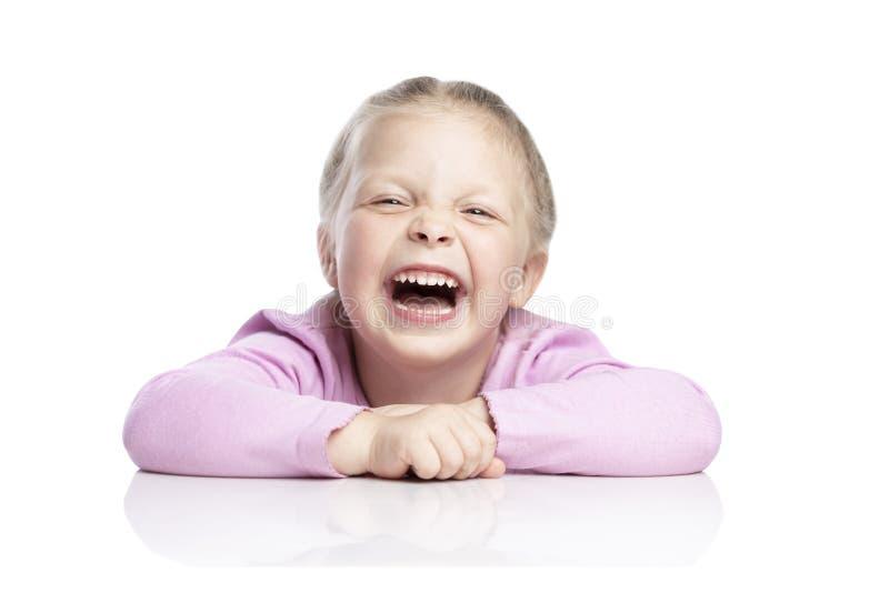 Piccolo ragazza bionda in un maglione rosa sta ridendo Primo piano Isolato sopra fondo bianco immagini stock