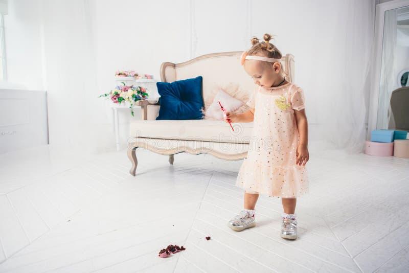 Piccolo ragazza caucasica divertente del bambino ? caduto sul dolce e sul disordine del dessert della dolcezza del pavimento L'as fotografia stock libera da diritti