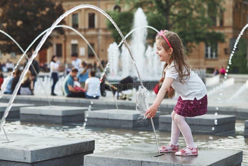 Piccolo ragazza felice che gioca con acqua in fontana nel centro della città fotografia stock