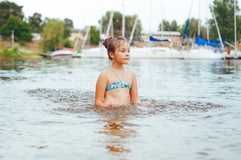 Piccolo ragazza felice gioca con acqua e spruzza dell'acqua nel mare immagine stock libera da diritti