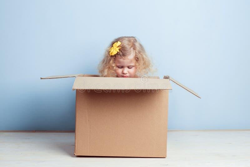 Piccolo ragazza riccia con il fiore giallo sui suoi capelli si siede nella scatola di cartone sui precedenti della parete blu immagini stock