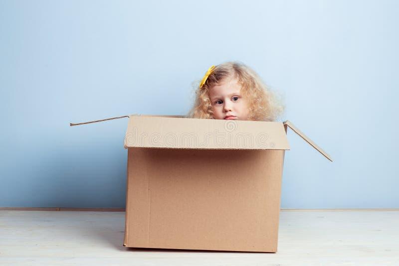 Piccolo ragazza riccia con il fiore giallo sui suoi capelli si siede nella scatola di cartone sui precedenti della parete blu immagine stock libera da diritti