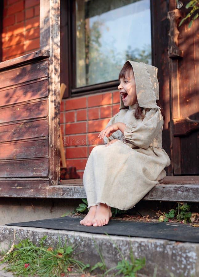 Piccolo ragazza scalza in un vecchio vestito dalla tela alla soglia della casa fotografia stock libera da diritti