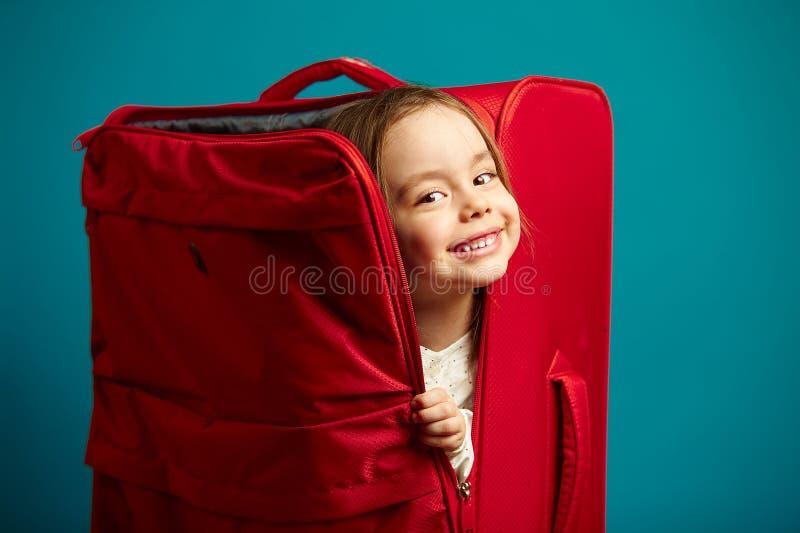Piccolo ragazza sorridente guarda dalla valigia rossa, ritratto del bambino allegro su fondo isolato blu immagine stock libera da diritti