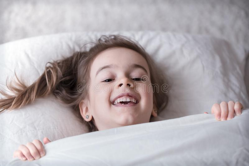 Piccolo ragazza sveglia che sorride a letto, concetto di sonno fotografia stock libera da diritti