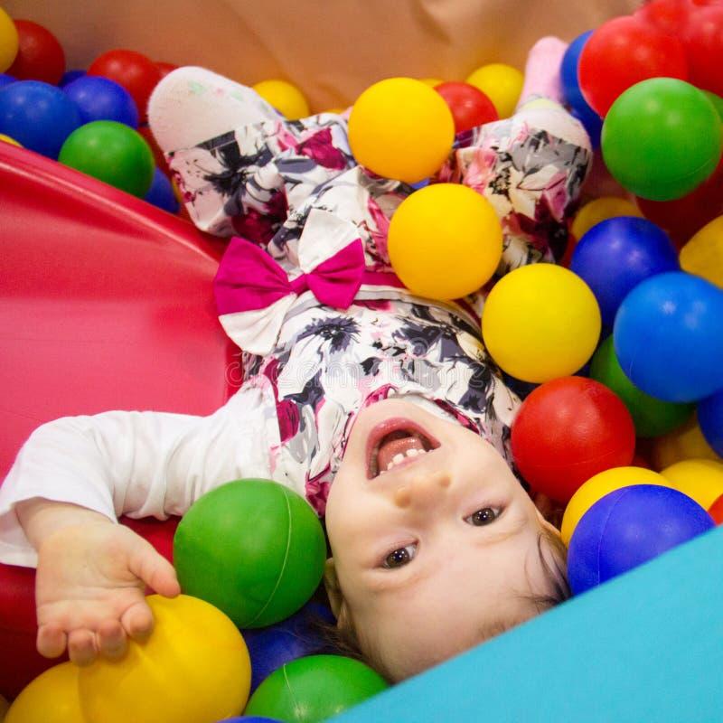 Piccolo ragazza sveglia di sorriso gioca in palle per uno stagno asciutto Stanza del gioco felicità immagini stock