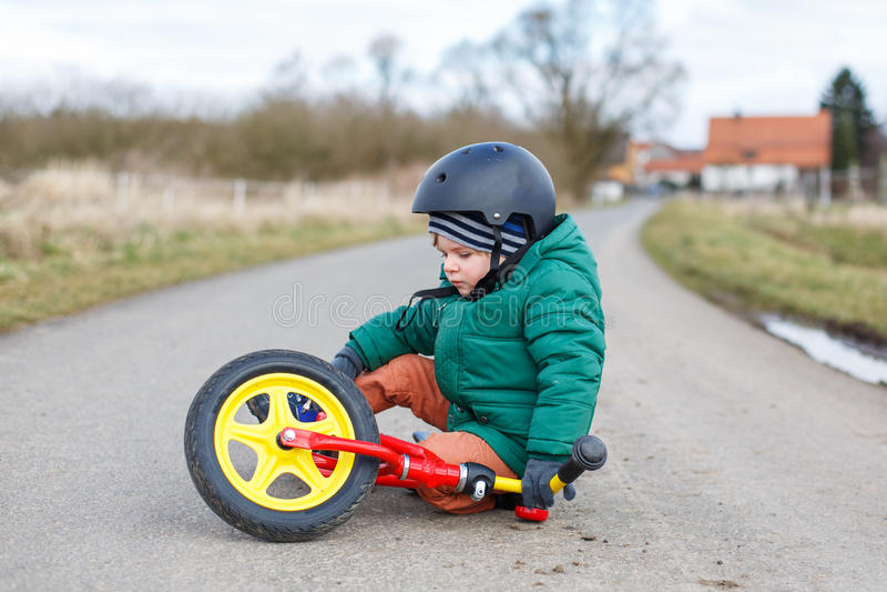 Piccolo ragazzo adorabile triste circa la sua bicicletta rotta, sittin del bambino fotografie stock libere da diritti
