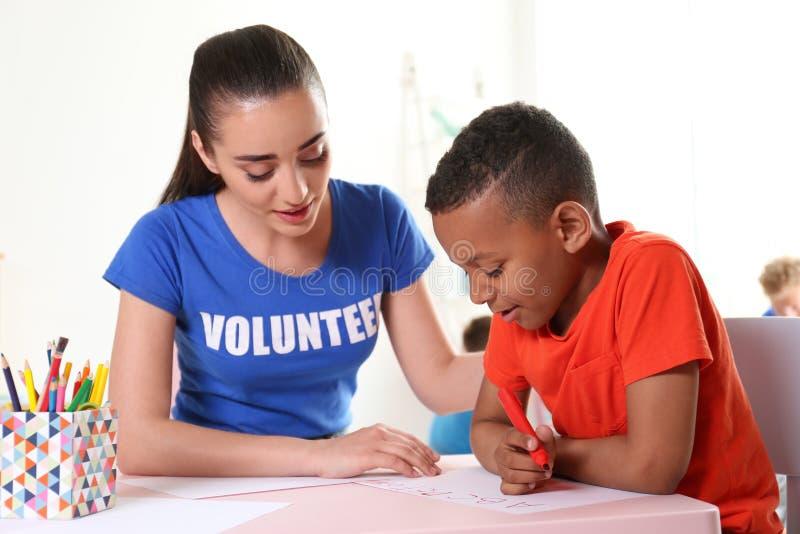 Piccolo ragazzo afroamericano che impara alfabeto con alla tavola all'interno fotografia stock libera da diritti