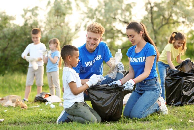 Piccolo ragazzo afroamericano che raccoglie rifiuti con i volontari fotografia stock