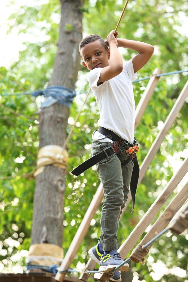 Piccolo ragazzo afroamericano che scala nel parco di avventura fotografia stock libera da diritti