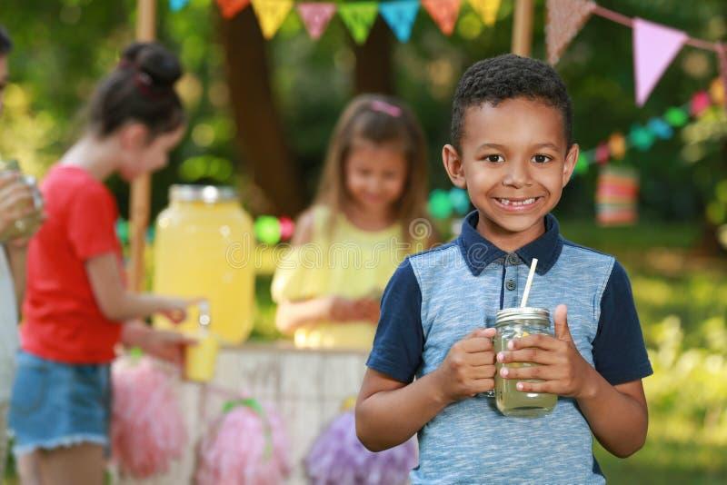 Piccolo ragazzo afroamericano sveglio con limonata naturale in parco Bevanda di rinfresco di estate immagini stock libere da diritti