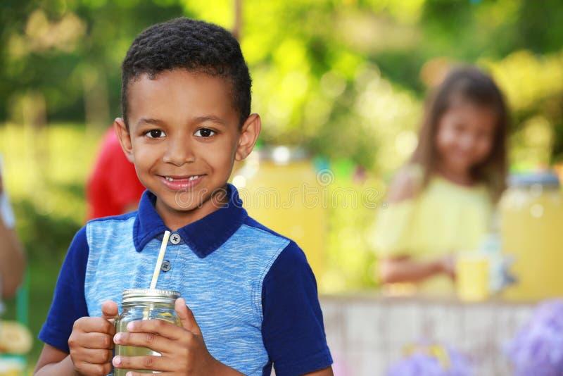 Piccolo ragazzo afroamericano sveglio con limonata naturale in parco, spazio per testo Rinfresco di estate immagine stock libera da diritti