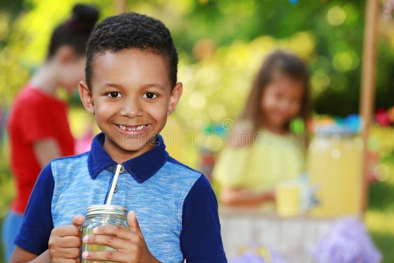 Piccolo ragazzo afroamericano sveglio con limonata naturale in parco, spazio per testo Rinfresco di estate fotografie stock