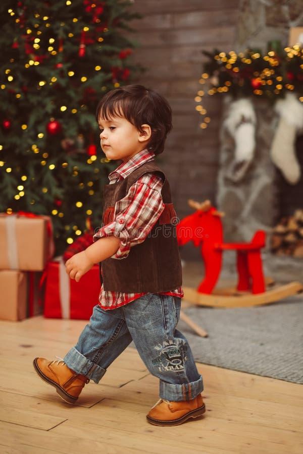 Piccolo ragazzo alla moda che cammina vicino all'albero di Natale fotografia stock libera da diritti
