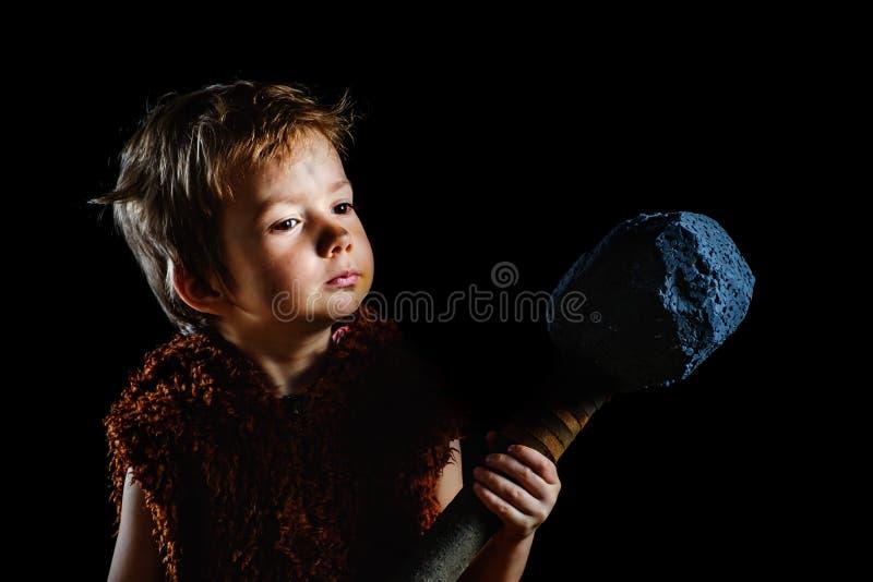 Piccolo ragazzo arrabbiato divertente del guerriero Neandertaliano o un'Ass.Comm.-Magnon Cavernicolo antico, maschio fotografie stock libere da diritti