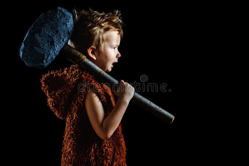 Piccolo ragazzo arrabbiato divertente del guerriero Neandertaliano o un'Ass.Comm.-Magnon Cavernicolo antico, senza camicia antico immagine stock