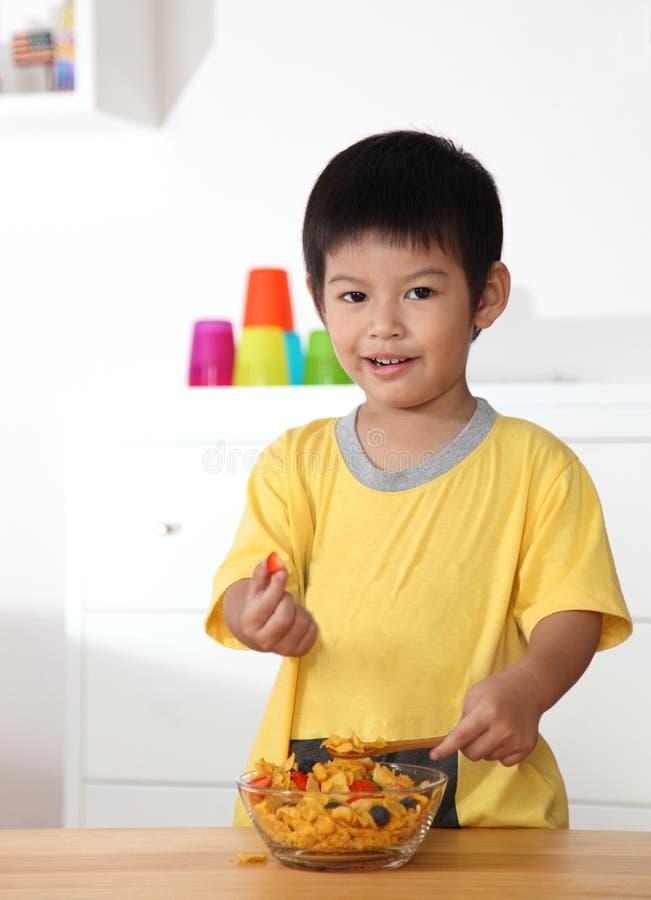 Piccolo ragazzo asiatico che mangia prima colazione sulla tavola di legno nella casa fotografia stock