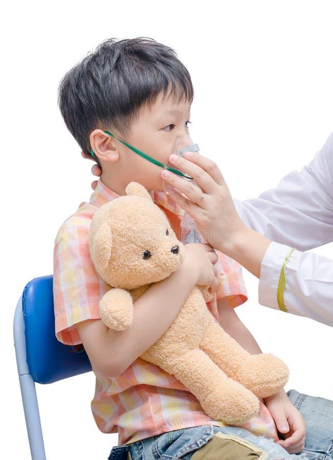 Piccolo ragazzo asiatico con asma facendo uso della maschera di ossigeno fotografie stock