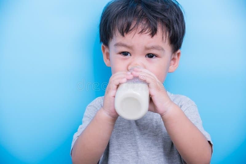 Piccolo ragazzo asiatico del bambino del bambino un latte alimentare da circa 2 anni da vetro da bottiglia immagini stock