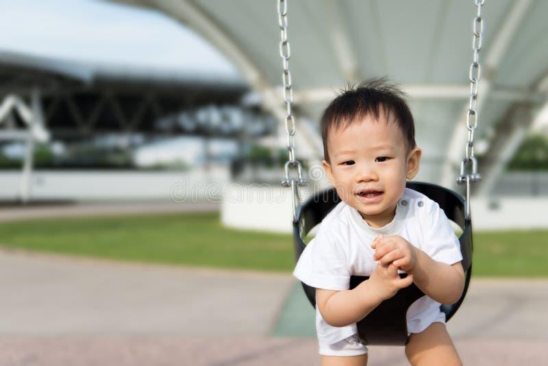 Piccolo ragazzo asiatico nell'oscillazione fotografia stock