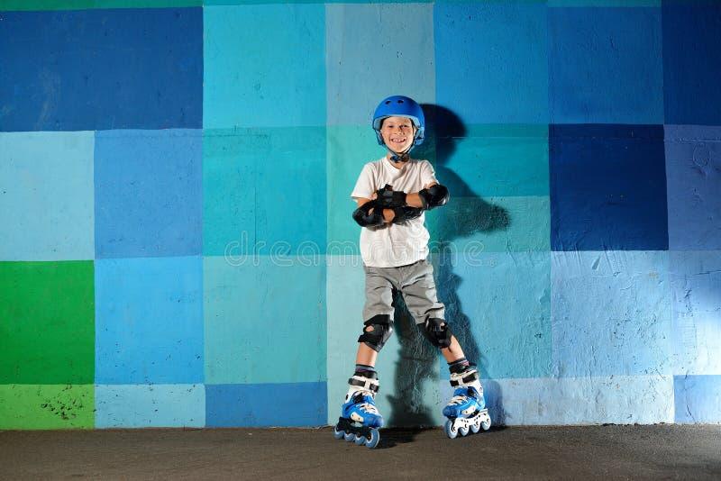 Piccolo ragazzo atletico sveglio sul rullo che sta contro la parete blu dei graffiti immagine stock