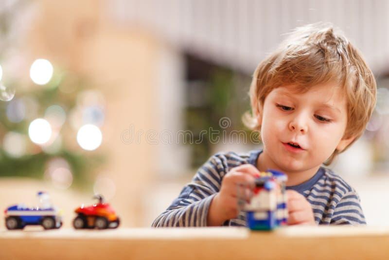 Piccolo ragazzo biondo che gioca con le automobili   fotografia stock libera da diritti