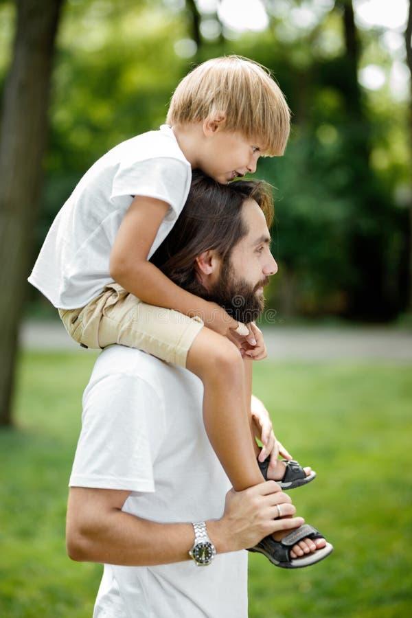 Piccolo ragazzo biondo che porta una maglietta bianca che si siede sulle spalle di suo padre barbuto bello immagine stock libera da diritti