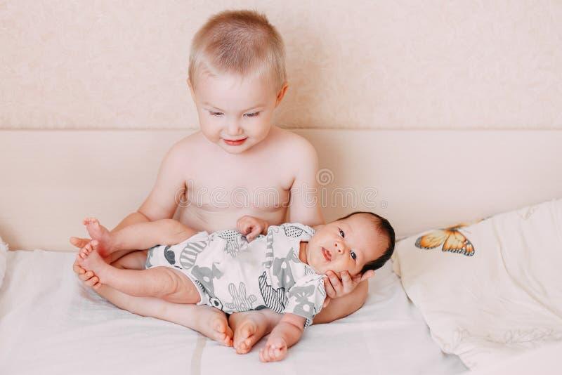piccolo ragazzo biondo più anziano del fratello del bambino che tiene sua sorella del bambino fotografia stock