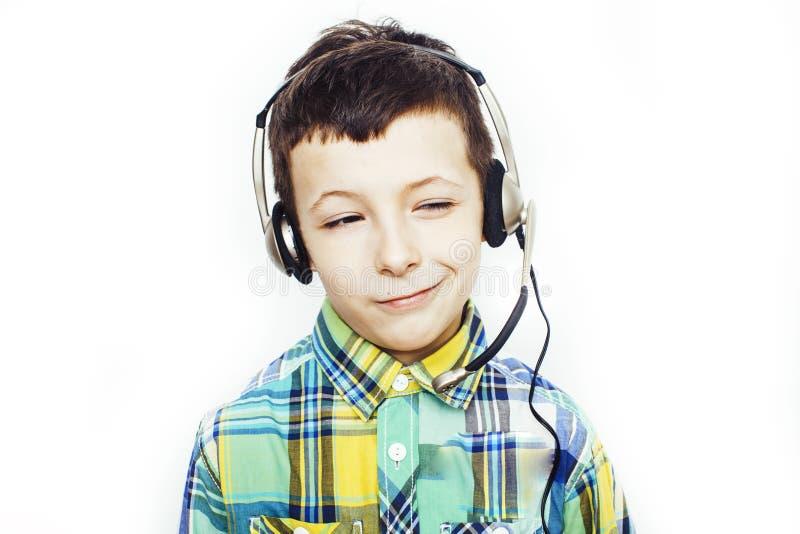 Piccolo ragazzo caucasico sveglio in cuffie che posano sorridere felice isolato su fondo bianco, concetto della gente di stile di fotografia stock