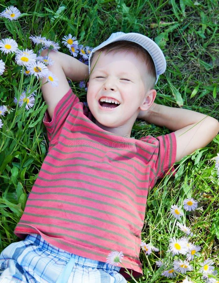 Piccolo ragazzo che si trova sull'erba immagini stock