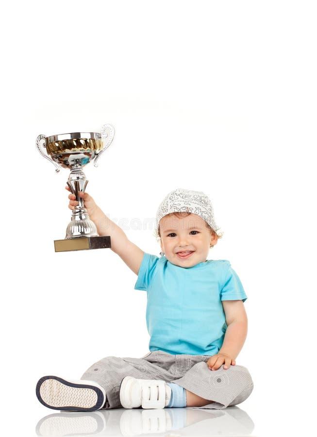 Piccolo ragazzo che tiene una tazza dei vincitori fotografie stock libere da diritti