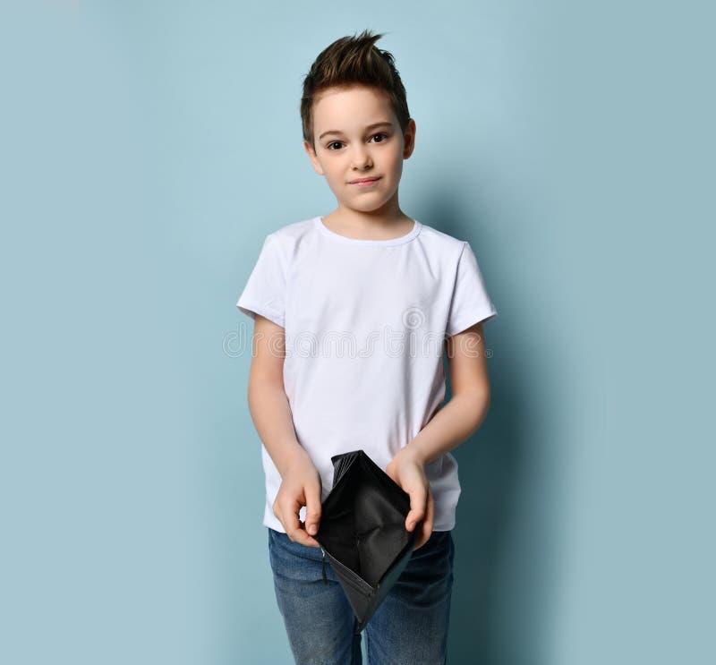 Piccolo ragazzo con capelli moderni in eleganti abiti casuali in piedi e con borsetta vuota fotografia stock