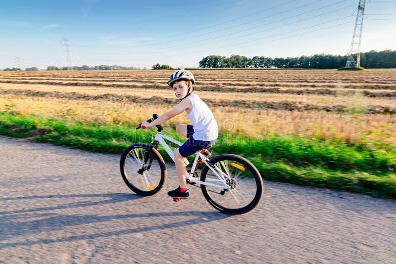 Piccolo ragazzo del bambino in casco bianco che guida la sua bicicletta immagini stock libere da diritti