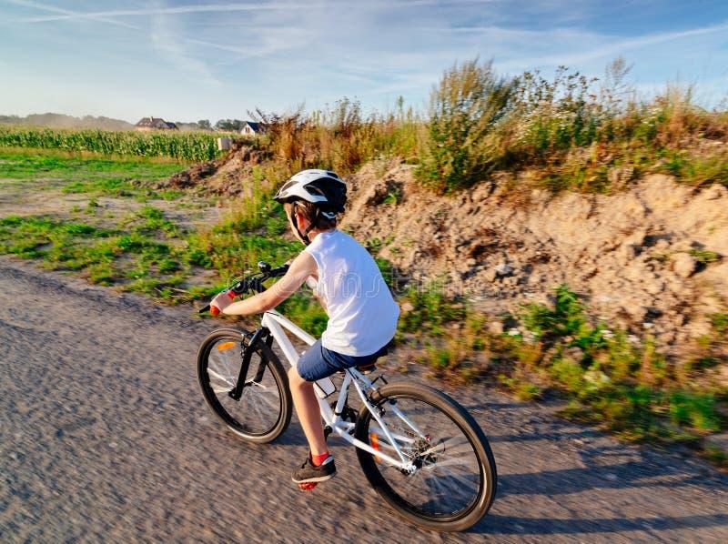 Piccolo ragazzo del bambino in casco bianco che guida la sua bicicletta immagini stock