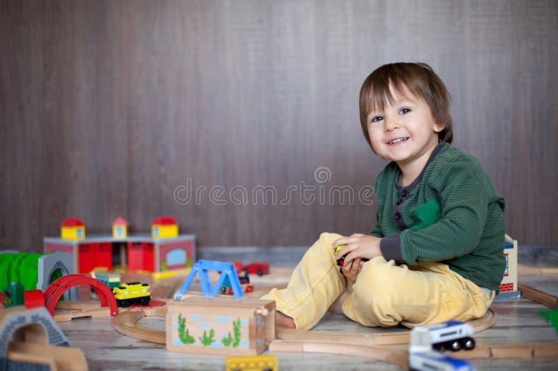 Piccolo ragazzo del bambino che gioca con la ferrovia di legno immagini stock libere da diritti