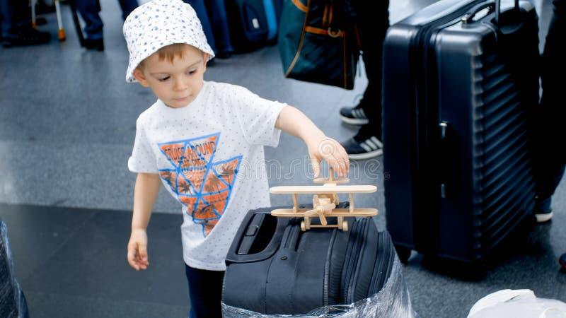 Piccolo ragazzo del bambino che sta nella coda di registrazione e che gioca con l'aeroplano di legno del giocattolo Viaggio del b immagine stock libera da diritti