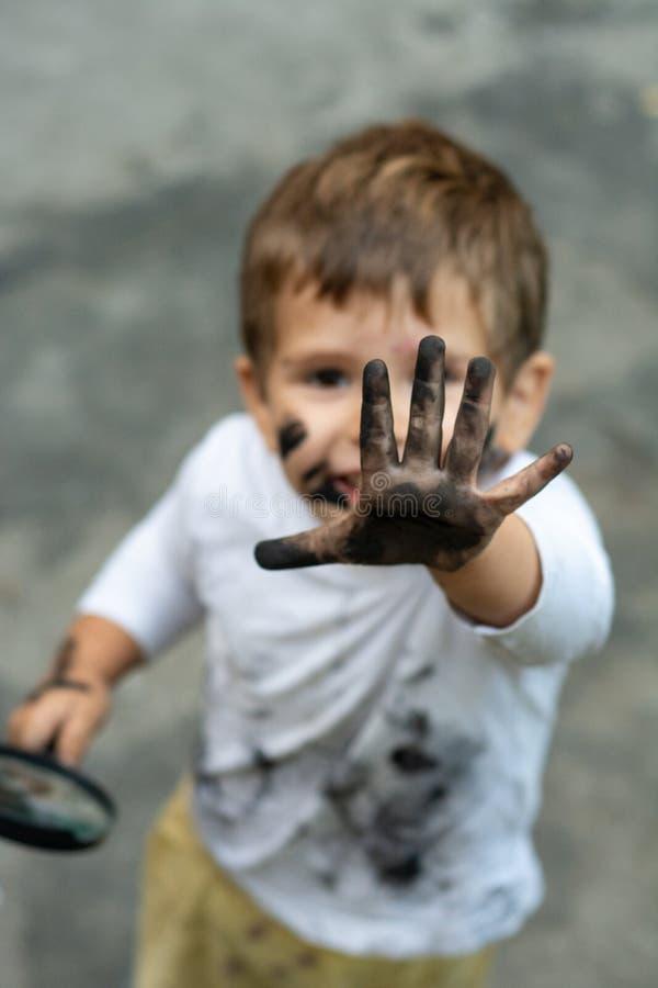 Piccolo ragazzo del bambino con il fronte sporco ed i vestiti sporchi che guardano tramite una lente d'ingrandimento sulla natura fotografie stock libere da diritti