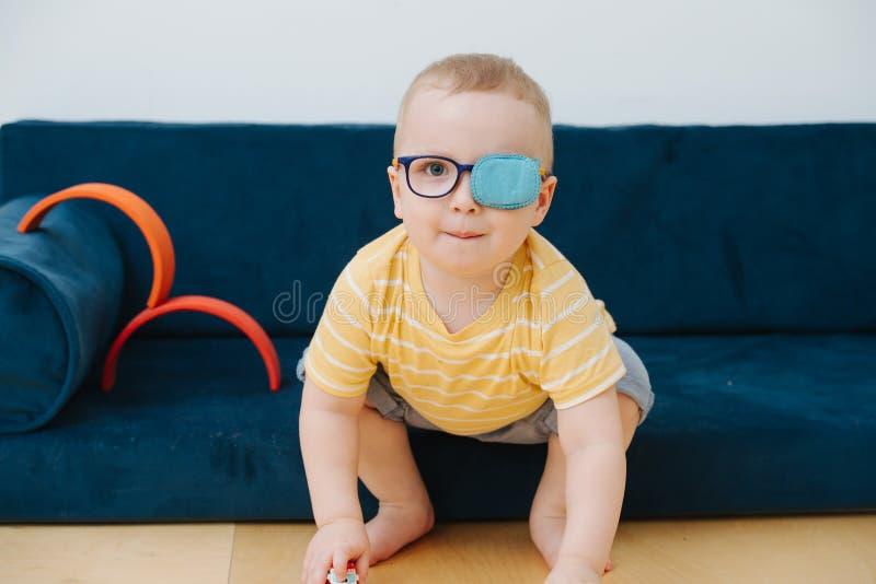 Piccolo ragazzo del bambino nella toppa pigra dell'occhio sta giocando con le automobili del giocattolo fotografie stock