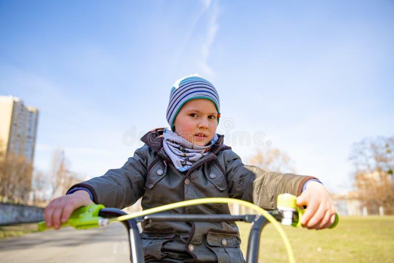 Piccolo ragazzo del bambino sulla bicicletta in parco all'aperto Un bambino sta guidando una bici dei bambini immagine stock libera da diritti