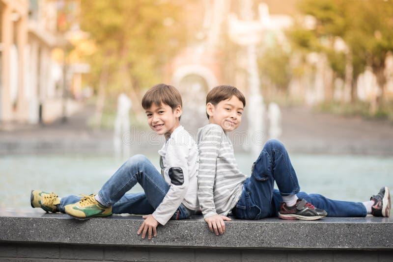 Piccolo ragazzo del fratello germano che si siede insieme alla fontana all'aperto immagini stock