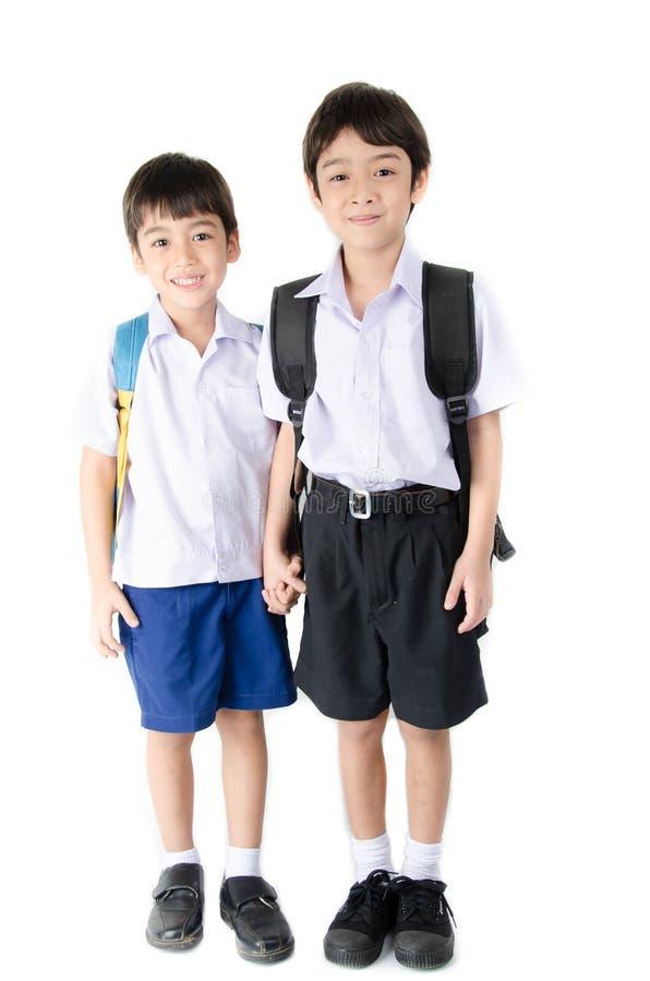 Piccolo ragazzo del fratello germano dello studente in uniforme su fondo bianco fotografia stock
