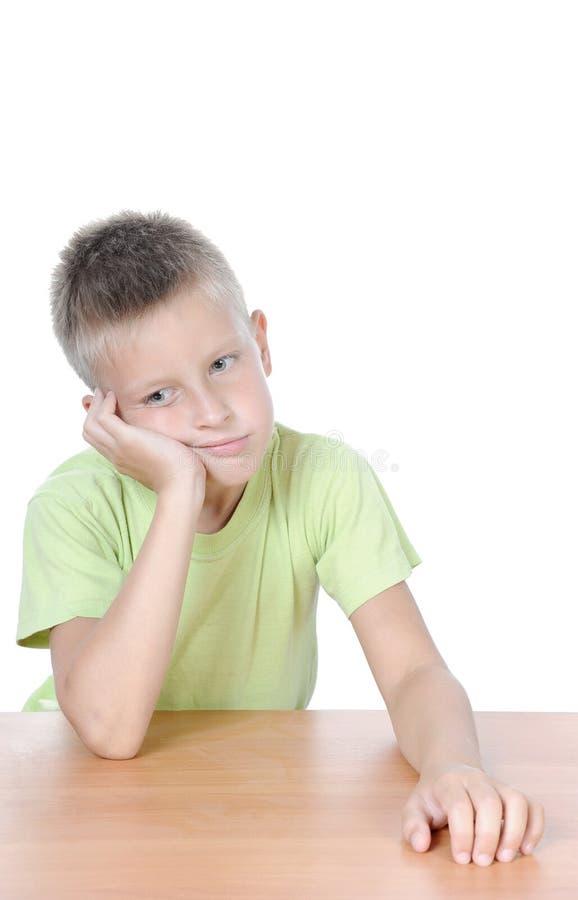 Piccolo ragazzo di pensiero alla tabella fotografia stock libera da diritti
