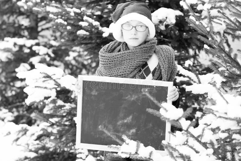 Piccolo ragazzo di Santa con la lavagna nell'inverno all'aperto immagini stock
