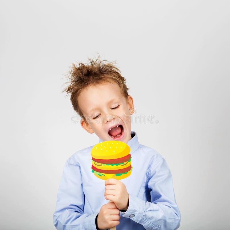 Piccolo ragazzo di scuola sveglio con l'hamburger di carta falso contro sedere bianche fotografie stock libere da diritti