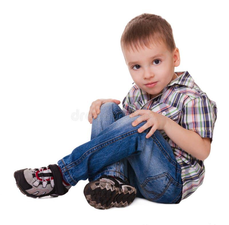 Piccolo ragazzo di seduta serio fotografie stock libere da diritti
