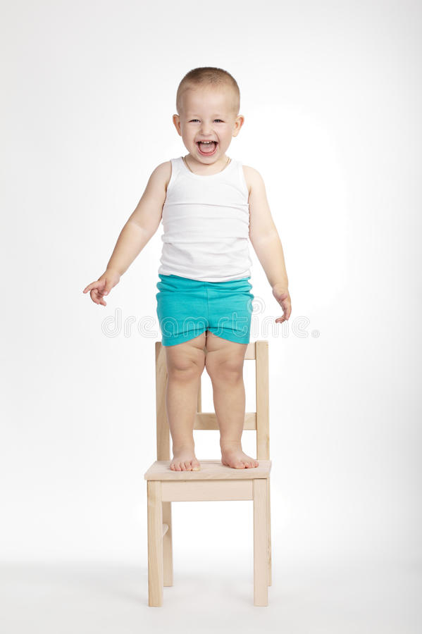 Piccolo ragazzo divertente sulla sedia fotografia stock libera da diritti