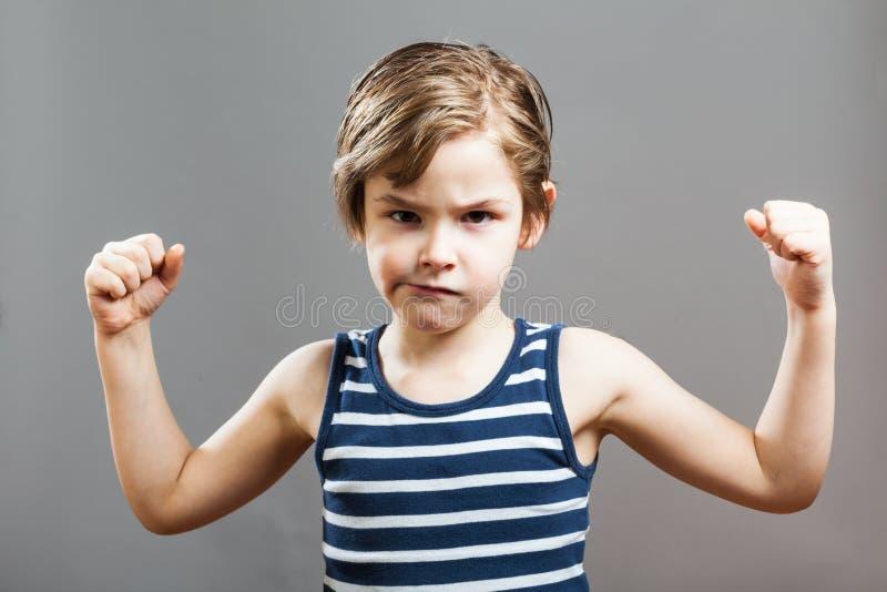 Piccolo ragazzo duro allegro, mostrante i suoi muscoli immagine stock libera da diritti