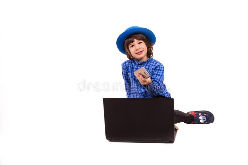 Piccolo ragazzo esecutivo allegro con lo Smart Phone ed il computer portatile immagine stock libera da diritti