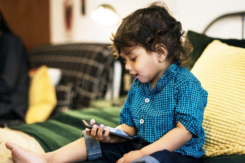 Piccolo ragazzo indiano che per mezzo del telefono cellulare fotografia stock